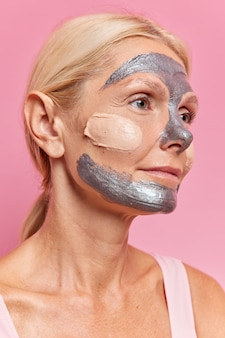 金髪のコーマをした真面目なヨーロッパ人女性の横向きのショットは、化粧品の手順を経て若返り、肌に栄養を与え、ピンクの壁に対して遠くのポーズに焦点を当てたシルバーマスクを適用します