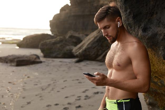 スマートフォンで深刻なスポーツマンのメッセージの横向きのショット、屋外でジョギングしています