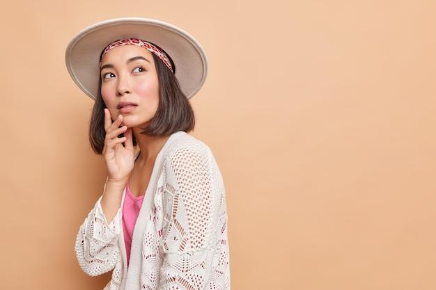 思いやりのある若いアジアの女性の横向きのショットは物思いにふける表情で目をそらします
