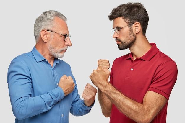 Боковой выстрел: двое мужчин, соперники серьезно смотрят друг на друга, держат руки сжатыми в кулаки, готовы к бою, не могут делиться общим делом, стоят у белой стены. люди и конкуренция
