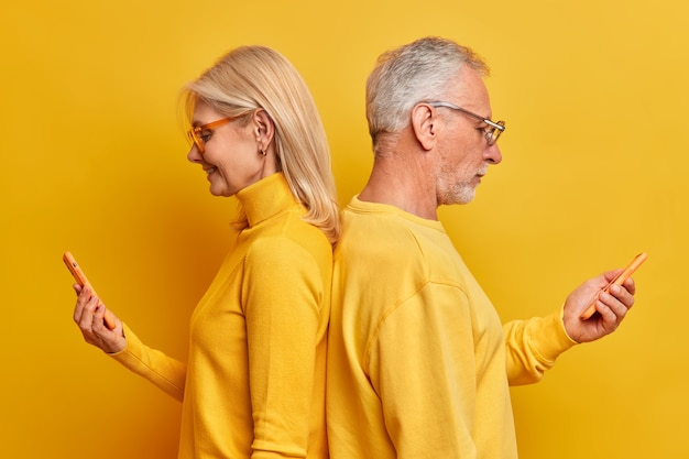 Sideways shot of old woman and man stands back to each other use modern smartphones chat online surf internet enjoy family time being addicted to technology isolated over yellow studio wall