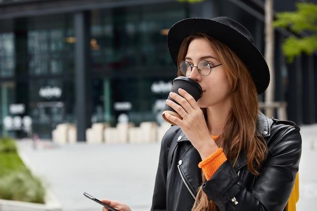Colpo laterale della ragazza pensierosa ha una pausa caffè dopo aver passeggiato per la città, tiene in mano il dispositivo smart phone, controlla la casella di posta elettronica, focalizzata a distanza