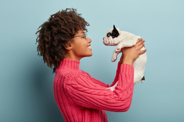 Sideways shot of playful positive afro female takes care of little pedigree dog who craves attention, wears spectacles, pink jumper pleased to have pet holds baby animal isolated over blue wall