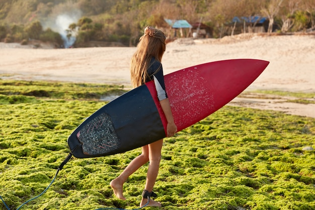 Sideways shot of professional goofy carries surfboard with leash