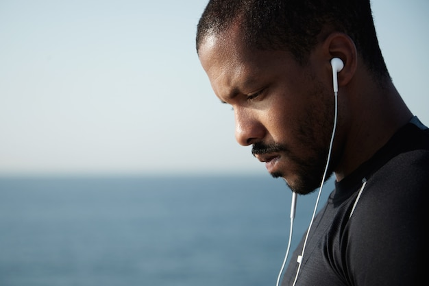 Sideways shot of sad african american man looking down and listening to melancholic music in headphones with serious, pensive face.
