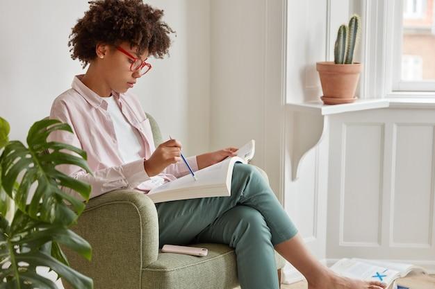 Colpo laterale di una donna intelligente afroamericana seria studia letteratura specifica, si siede in poltrona contro interni accoglienti, tiene una matita