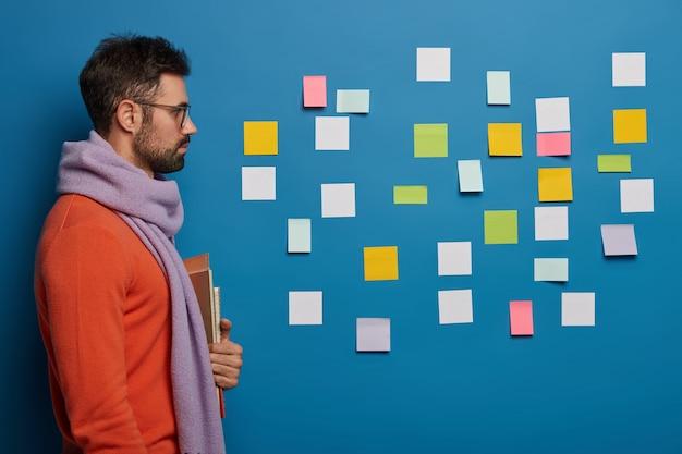Colpo laterale di studente barbuto serio indossa sciarpa, maglione, tiene libri, guarda attentamente il muro blu con note adesive colorate pensa alle attività del progetto.