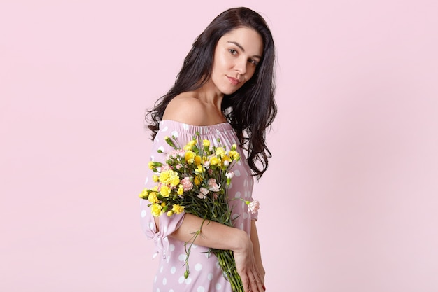 Sideways shot of serious dark haired woman with healthy skin, holds bouquet, dressed in fashionable dress, poses on pastel pink. spring is coming. international womens day