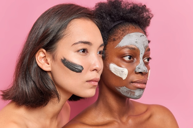 Sideways shot of serious multiethnic women concentrated into distance apply clay mask on faces undergo beauty procedures prepare for date want to look young stand shirtless against pink wall