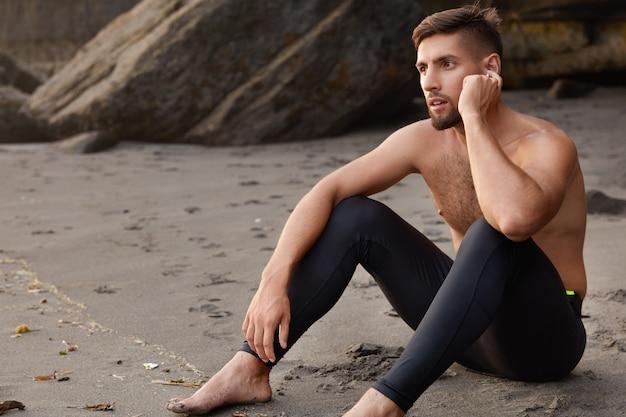 Colpo laterale di uno sportivo serio con la barba lunga si siede sulla spiaggia sabbiosa