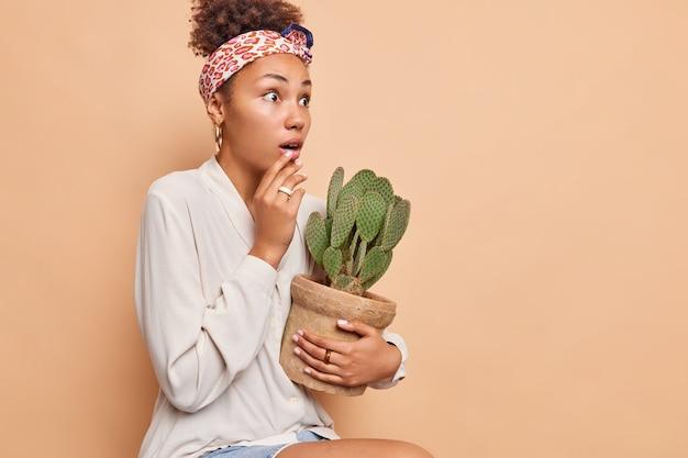 Colpo laterale della donna sorpresa fissa impressionata trattiene il respiro trattiene il cactus in vaso si sente impressionato indossa il fazzoletto legato sopra la testa camicia bianca isolata sul muro beige copia spazio