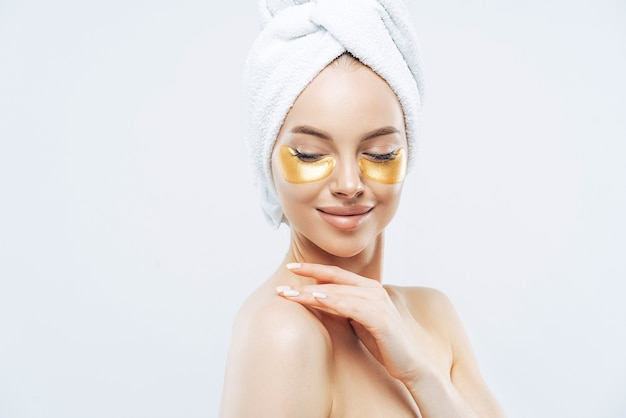Sideways shot of tender young woman with eye collagen gold pads, healthy fresh skin, anti aging moisturising mask, touches shoulder gently, wears bath towel on head, isolated over white studio wall