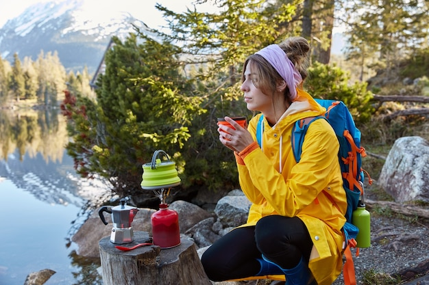 Sideways shot of thoughtful traveller enjoys hot drink from disposable cup near mountain lake, being deep in thoughts