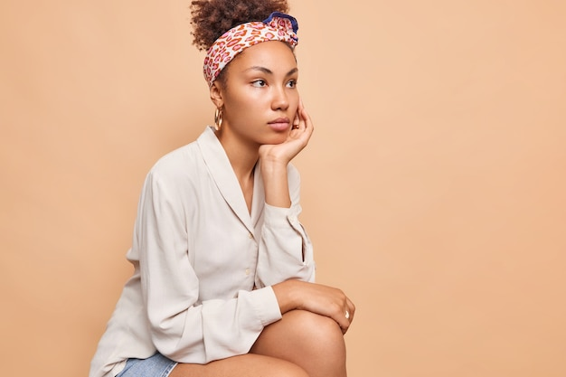 Sideways shot of thoughtful woman concentrated into distance has combed curly hair wears headband white shirt plans something holds hand under chin isolated over beige wall