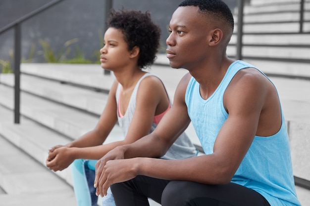 Sideways shot of two black youngsters looks thoughtfully somewhere, pose at stairs, have athletic body, train together, prepare for competition, have thoughtful expressions. relaxed athletic people
