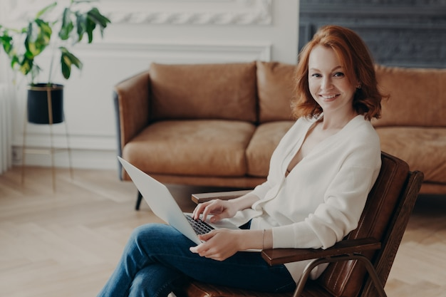 Sideways shot of woman entrepreneur sits in comfortable armchair in modern apartment with luxury furtniture, communicates with colleague through online video chat, uses laptop free internet connection