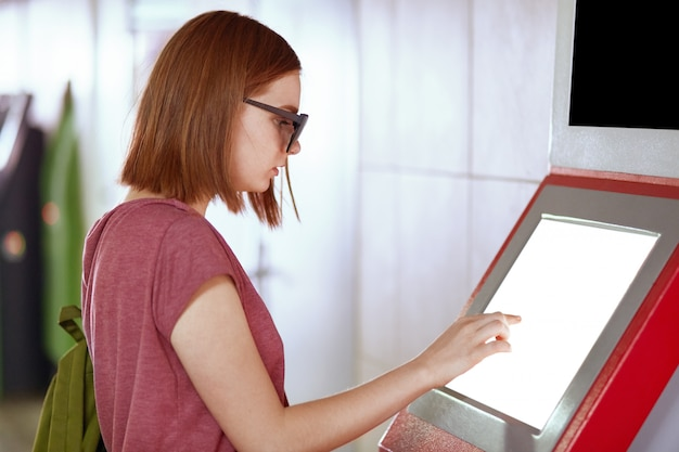 Sideways shot of young caucasian female with bobbed hairstyle, wears trendy shades, uses atm machine for withdrawing money, carries rucksack, types code on empty blank screen for your information