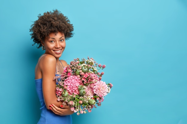 Sideways shot of young woman wears dress holds bouquet of flowers gets it as present on 8 march poses against blue wall with copy space for your promotion