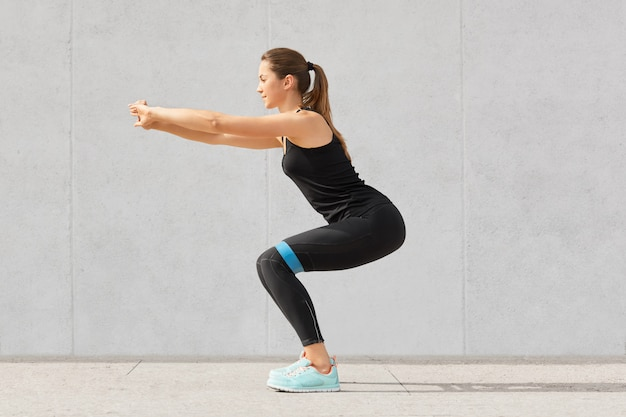 Sideways sporty european young woman has workout with rubber band, dressed in black sportsclothes, has exercises for buttocks, poses on grey. motivation concept.