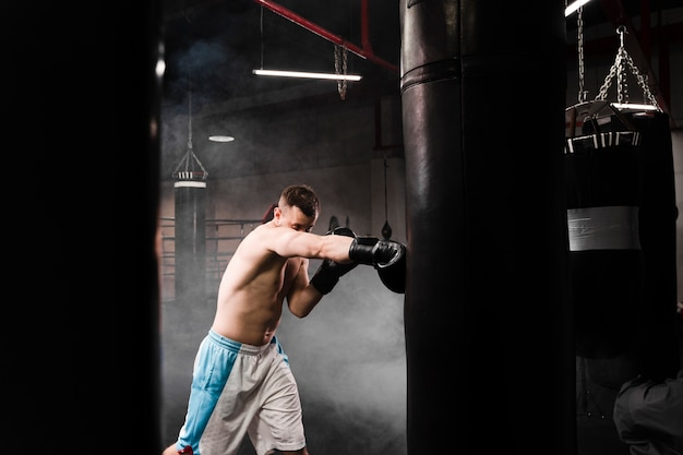 Sideways strong male boxer training for a competition