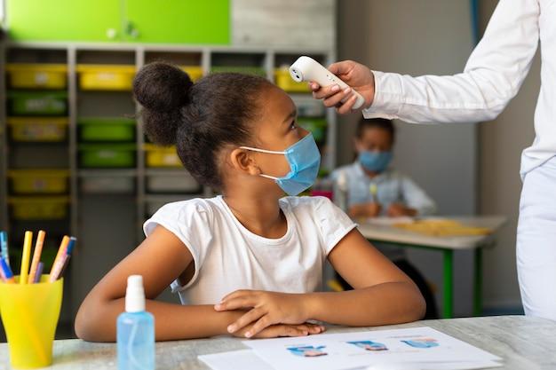 Боковой учитель измеряет температуру ученика