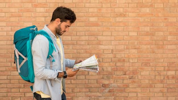 Sideways traveler looking on map