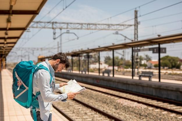 Боком путешественник смотрит на карту
