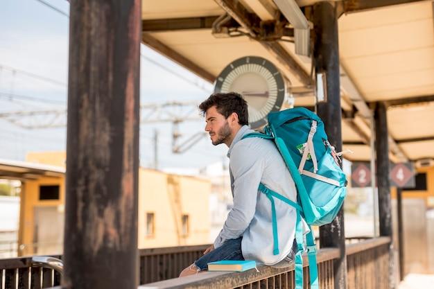 Sideways traveler waiting for train