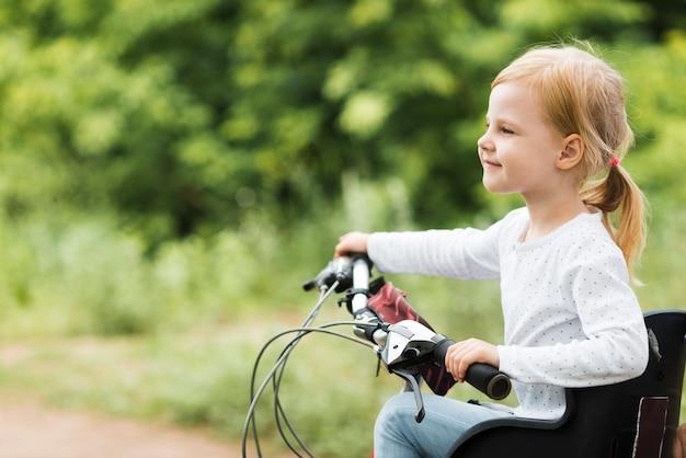 Боком смотреть маленькая девочка на велосипеде