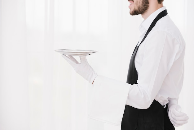 Sideways waiter holding metal plate