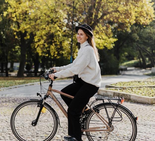 Сбоку женщина и велосипед альтернативный транспорт