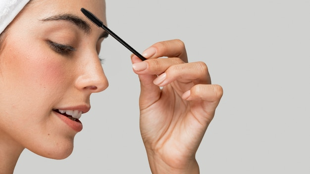Sideways woman applying mascara on her lashes