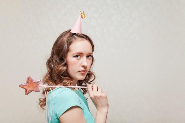 Sideways woman in blue dress wearing a party hat