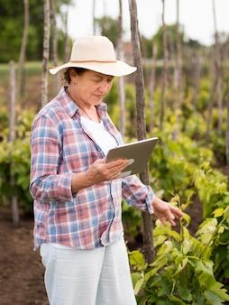 Боком женщина проверяет свой сад