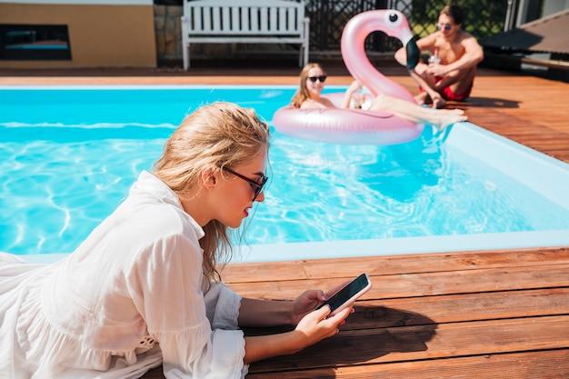옆으로 여자는 수영장에서 그녀의 전화를 확인