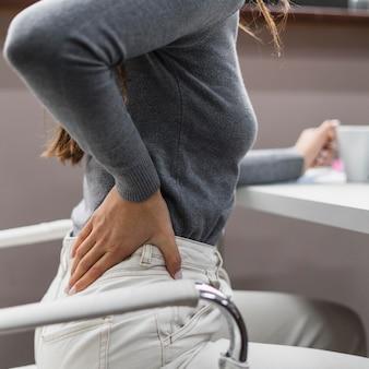 Боковая женщина болит спина во время работы из дома