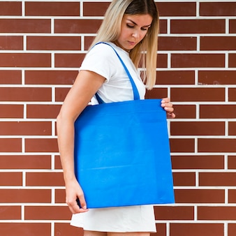 Sideways woman holding a blue bag