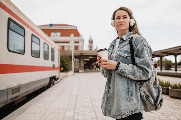 電車のホームで音楽を聴いている横向きの女性