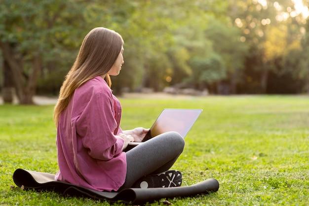 公園で自分のラップトップを見ている横向きの女性