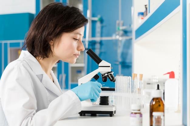Боком женщина смотрит в микроскоп