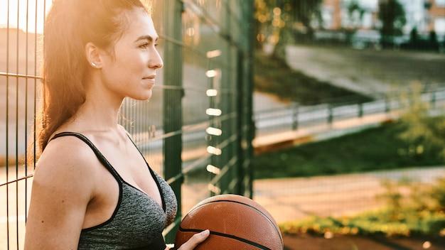 Боком женщина играет в баскетбол в одиночку