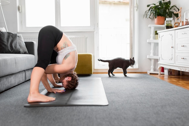 Sideways woman practicing yoga and cat at home