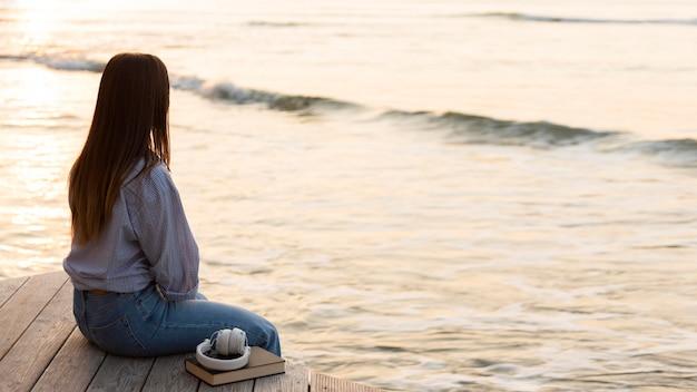 Боком женщина сидит и смотрит на море