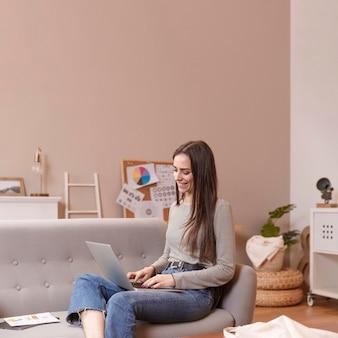 Боком женщина сидит на диване и работает