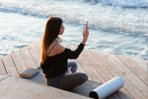 Donna di lato che scatta una foto del mare