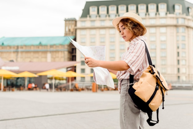 Sideways woman traveling alone with a map