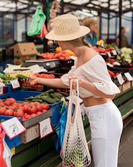 Sideways woman using organic bag for veggies