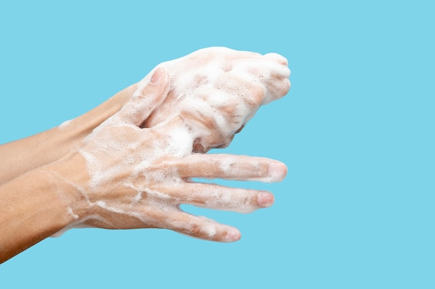 Sideways woman washing her hands on blue background with copy space