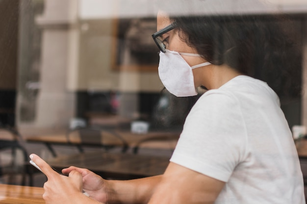Sideways woman with medical mask checking her phone