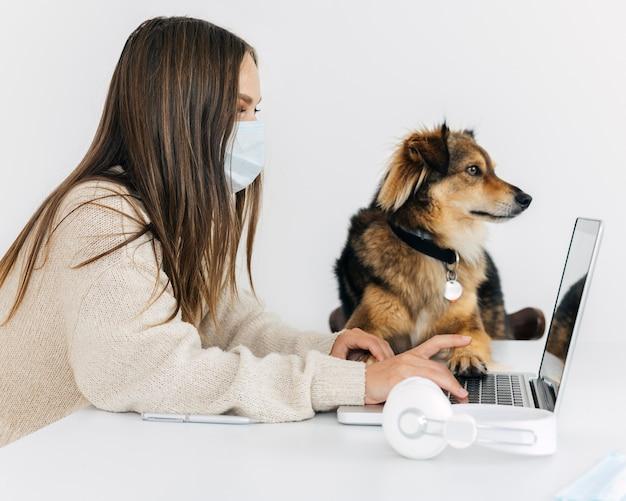 Боком женщина с медицинской маской играет со своей собакой